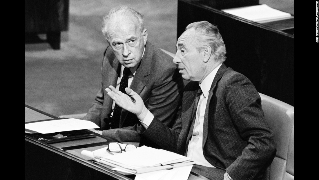Israeli Foreign Minister Shimon Peres, right, consults with Defense Minister Yitzhak Rabin on November 26, 1986, during a vote in the Israeli parliament, Knesset, about shipments of arms to Iran.
