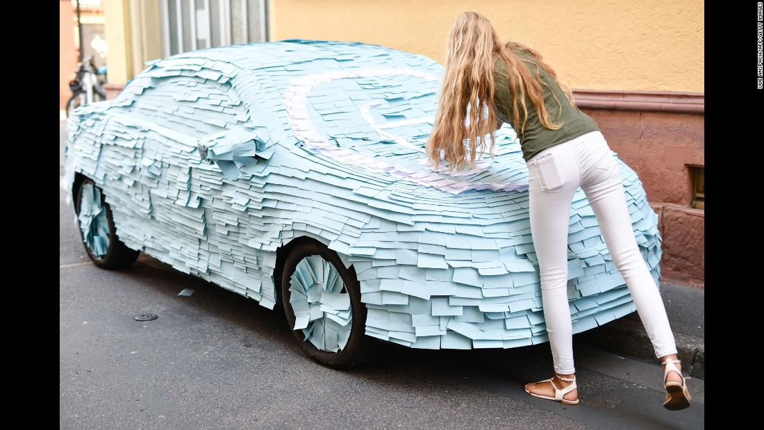 A woman sticks notes on an illegally parked car in Heidelberg, Germany, on Friday, September 9.