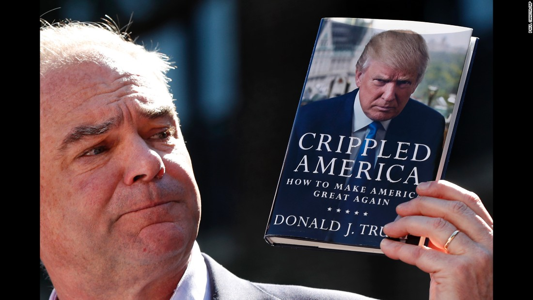 "Democratic vice presidential nominee Tim Kaine holds ""Crippled America,"" a book by Donald Trump, while speaking during a campaign rally in Ann Arbor, Michigan, on Tuesday, September 13."