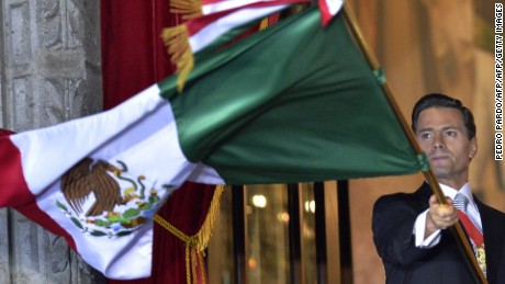 "Mexican President Enrique Pena Nieto waves the Mexican National Flag on the main balcony of the National Palace during ceremonies called ""The Shout"" marking the start of celebrations of Independence Day in Mexico City on September 15, 2016. / AFP PHOTO / Pedro PardoPEDRO PARDO/AFP/Getty Images"