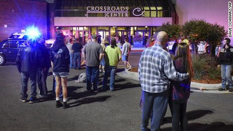 People stand near the entrance on the north side of Crossroads Center mall between Macy's and Target as officials investigate a reported multiple stabbing incident, Saturday, Sept. 17, 2016, in St. Cloud, Minn. Police said multiple people were injured at the St. Cloud shopping mall on Saturday evening in an attack possibly involving both shooting and stabbing. The suspect is believed to be dead, St. Cloud Police Sgt. Jason Burke told the St. Cloud Times. (Dave Schwarz/St. Cloud Times via AP)