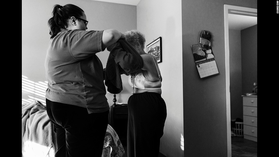 An employee at the memory care facility helps Eloise get dressed.