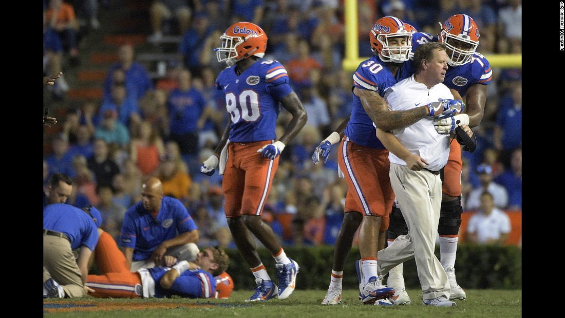 Florida head coach Jim McElwain is restrained by tight end DeAndre Goolsby and offensive lineman Fred Johnson after his quarterback, Luke Del Rio, was injured by a North Texas player on Saturday, September 17. North Texas was penalized for roughing the passer, and McElwain went to midfield to let the North Texas bench know he was not happy with the hit.