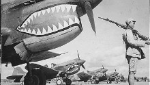 A Chinese soldier guards a line of American P-40 Flying Tiger fighter planes at an airfield somewhere in China.