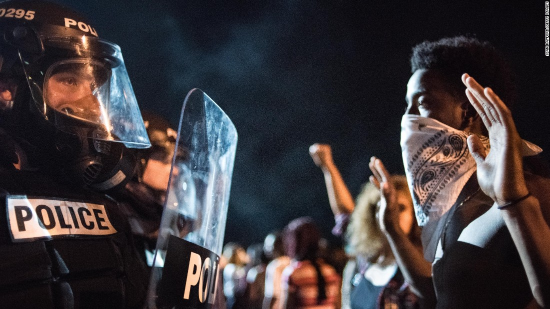 On the first night of demonstrations, police officers face off with protesters on Interstate 85.