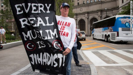 A Donald Trump supporter holds up an anti-Muslim poster as he awaits anti-Donald Trump protesters marching through the streets in Cleveland, Ohio,  near the Quicken Loans Arena site of the Republican National Convention July 18, 2016. / AFP / JIM WATSON        (Photo credit should read JIM WATSON/AFP/Getty Images)