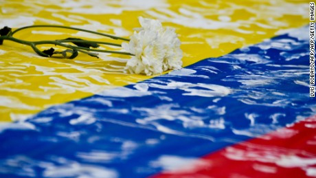 A flower remains on a Colombian national flag during a march along the streets of Cali, Colombia, on July 15, 2016, in support of the peace talks between the government of Colombian President Juan Manuel Santos and the FARC guerrillas, which takes place in Havana, Cuba.  Different social organizations held rallies in cities across the country Friday in the framework of a campaign to support the peace process. / AFP / LUIS ROBAYO        (Photo credit should read LUIS ROBAYO/AFP/Getty Images)