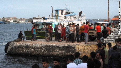 People gather at the port at Rashid on September 21 as the search continues