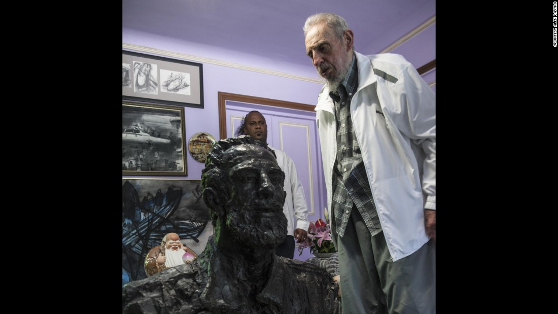 "Fidel Castro stands next a statue of himself given to the ex-Cuban president by a Chinese artist. Despite receiving gifts such as this, his father does not want ""a cult of personality,"" Castro's son and photographer Alex Castro says."