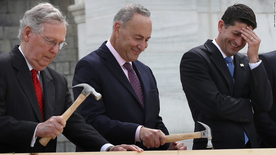House Speaker Paul Ryan laughs as Senate Majority Leader Mitch McConnell, left, and U.S. Sen. Chuck Schumer hammer ceremonial nails outside the U.S. Capitol on Wednesday, September 21. Construction has begun on the platform where the next President will be inaugurated.