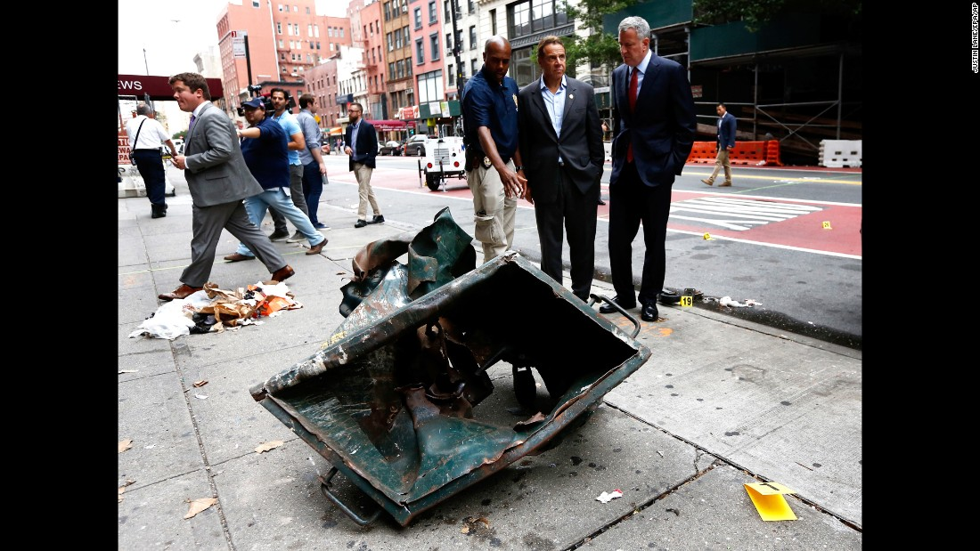 "New York Mayor Bill de Blasio, right, and New York Gov. Andrew Cuomo, second right, look over the mangled remains of a dumpster Sunday, September 18, in New York's Chelsea neighborhood. An explosion <a href=""http://www.cnn.com/2016/09/17/us/gallery/ny-explosion-0917/index.html"" target=""_blank"">injured 29 people there</a> the night before."