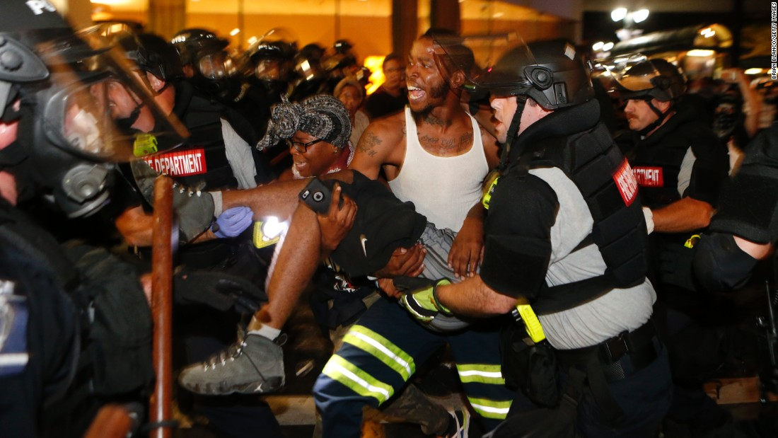 "Police officers and protesters carry a man who was shot during the second night of protests on Wednesday, September 21. The shooting victim, 26-year-old Justin Carr, later died. Police <a href=""http://www.cnn.com/2016/09/23/us/charlotte-protests/index.html"" target=""_blank"">have charged another civilian</a> in connection with Carr's death."