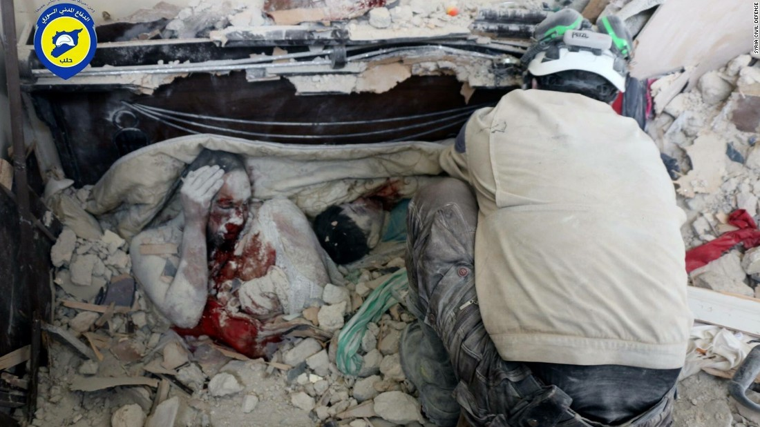 This photo was released by the volunteer group Syria Civil Defense of the bodies of a man, with his knee pulled up near his face, and a child covered in dust after they were killed in the airstrike.