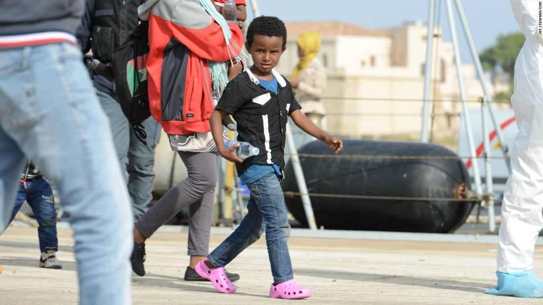 An excited young boy takes his first steps on land after several days at sea.