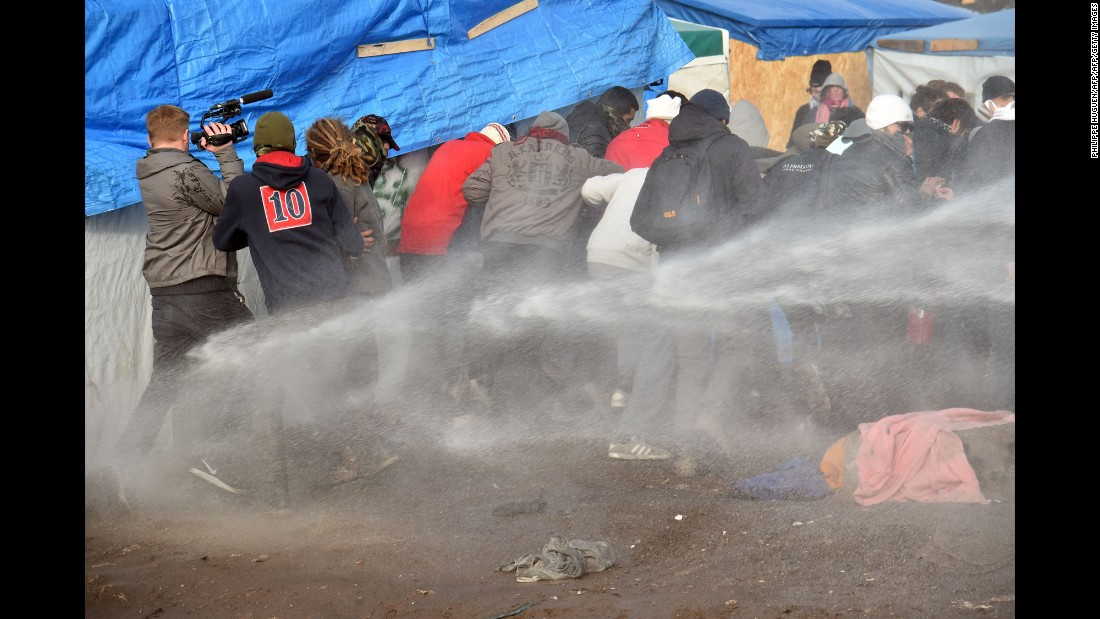 "Riot police spray water on migrants to disperse them during the dismantling of half of ""The Jungle"" on February 29."