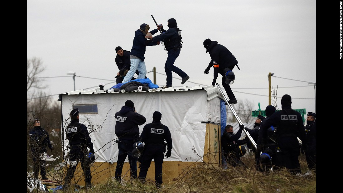 A woman fights with a police officer as she is removed from the top of a hut on March 1. Police and demolition teams were starting to dismantle makeshift shelters and relocating people to accommodations nearby.