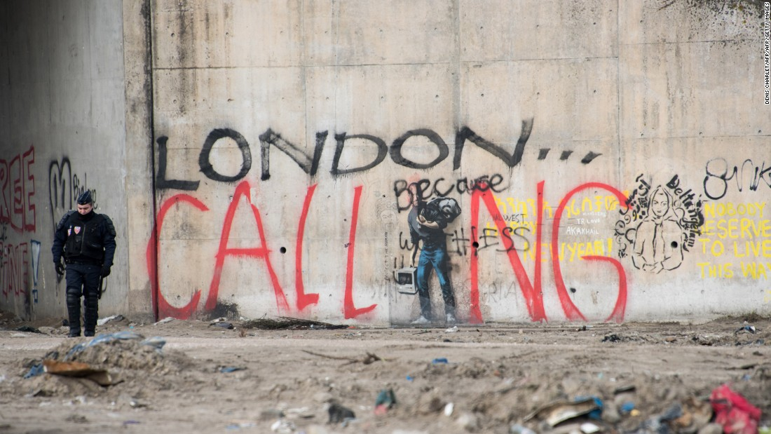 "A French riot policeman stands near graffiti during the dismantling of the southern part of ""The Jungle"" migrant camp on Thursday, March 10. The graffiti reads ""London calling,"" a reference to how the camp has become notorious for migrants and refugees trying to enter the UK illegally."