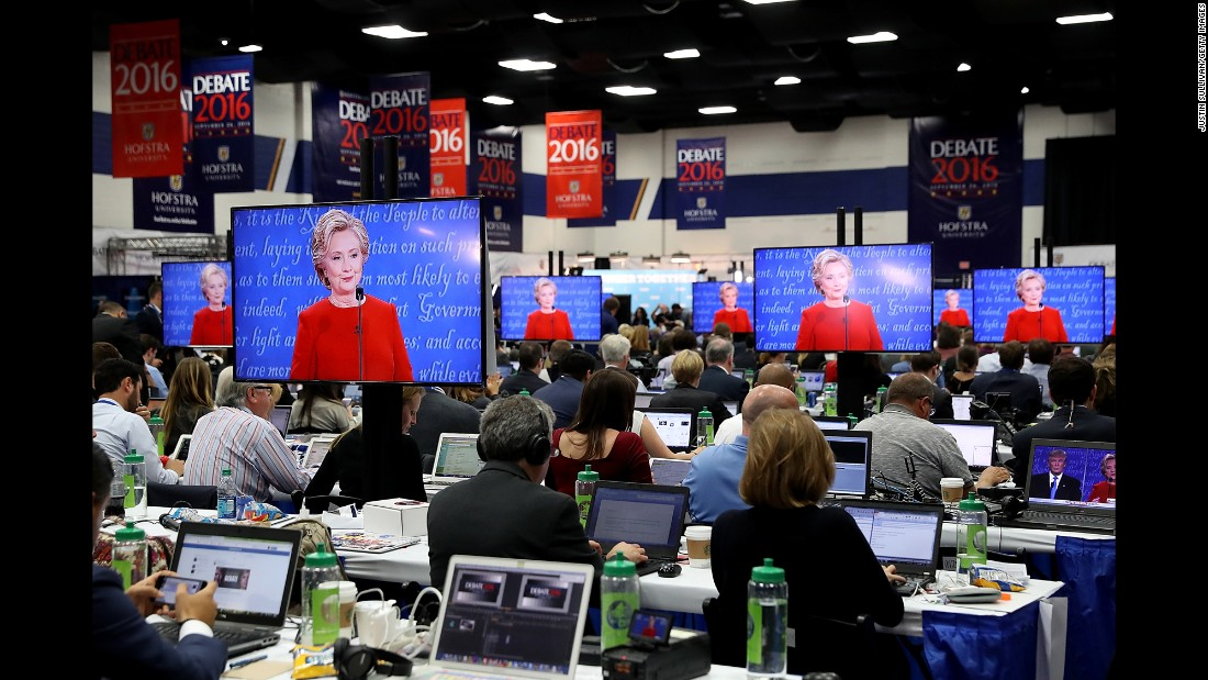 Clinton is seen on television monitors in the media center at Hofstra.