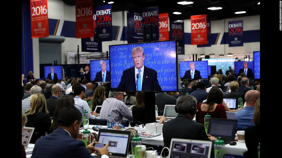 Trump appears on the media center screens.
