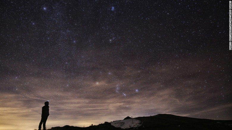 a photographer looks at the sky at night in northern italy during the 2015 geminid meteor