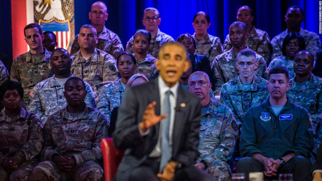 Military members watch Obama speak.
