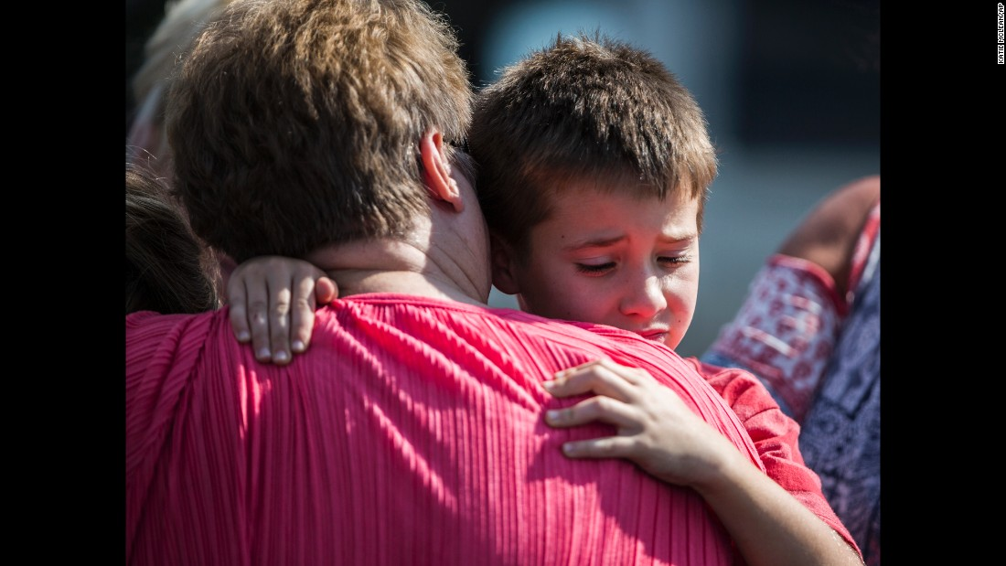 "A woman hugs a boy following <a href=""http://www.cnn.com/2016/09/28/us/south-carolina-elementary-school-shooting/"" target=""_blank"">a shooting at an elementary school</a> in Townville, South Carolina, on Wednesday, September 28. A teenager is suspected of opening fire at the school's playground, wounding two students and a teacher just one minute after placing a teary phone call that led to the discovery of his father's body at a nearby home."