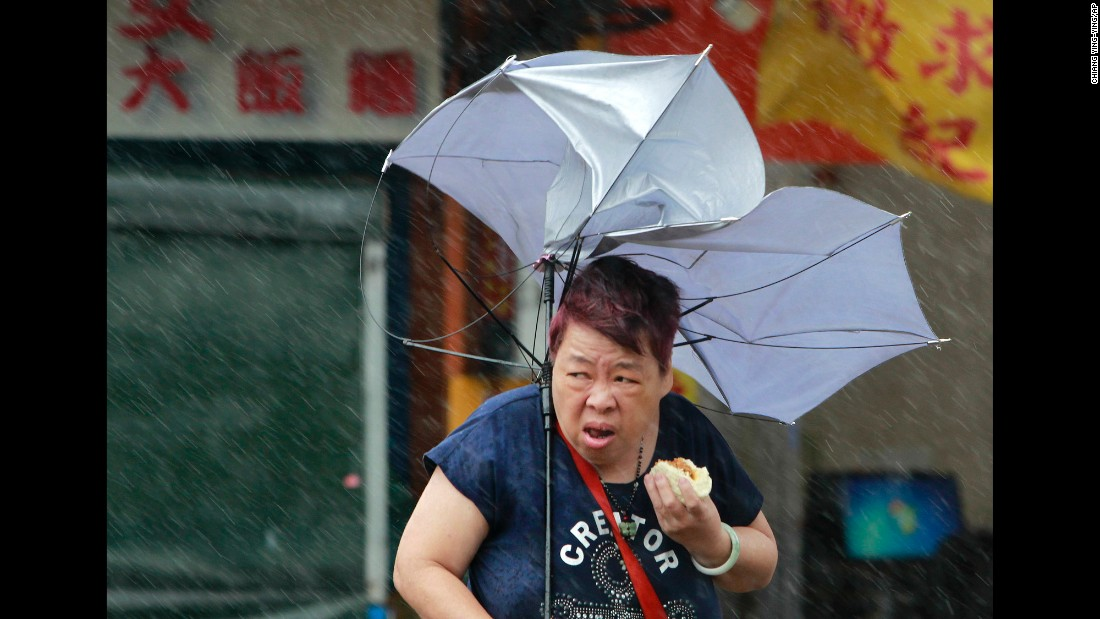 "A woman struggles with her umbrella as she eats food in Taipei, Taiwan, on Tuesday, September 27. Typhoon Megi brought powerful winds to the island before <a href=""http://www.cnn.com/2016/09/26/asia/typhoon-megi-taiwan-weather/index.html"" target=""_blank"">making landfall in mainland China.</a>"
