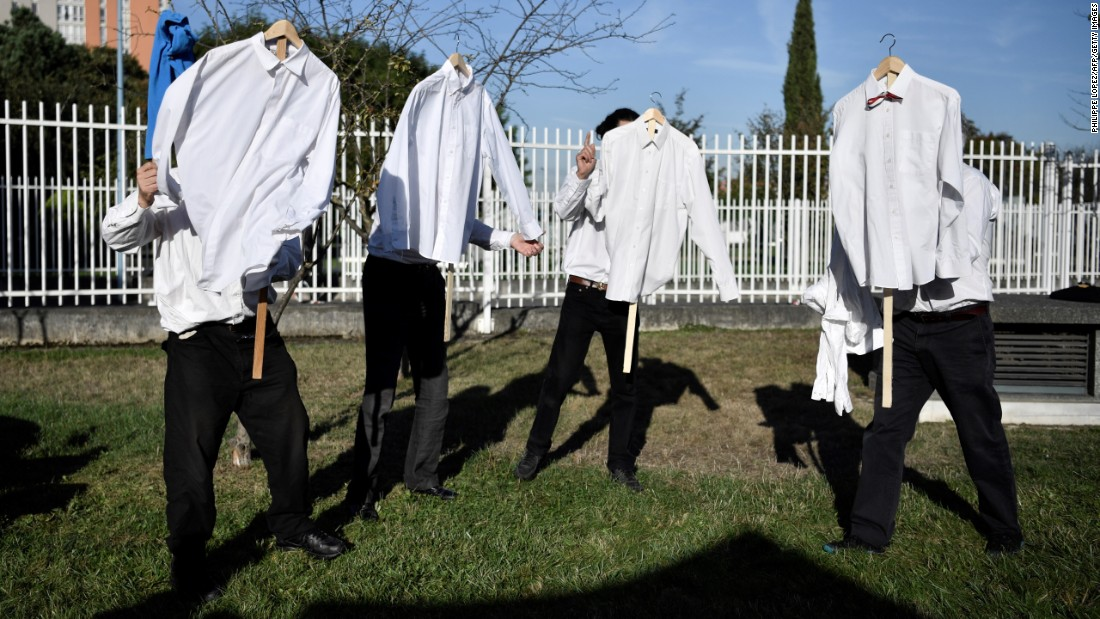 Performers from a small theater company hold shirts as they rehearse their act near the courthouse in Bobigny, France, on Tuesday, September 27. At the courthouse, some Air France workers were on trial for an incident last year where two airline executives had their shirts ripped off during a protest over job cuts.