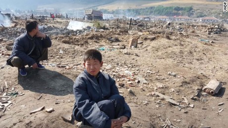A young North Korean boy sits amid a flood-ravaged landscape in Hamgyong province.
