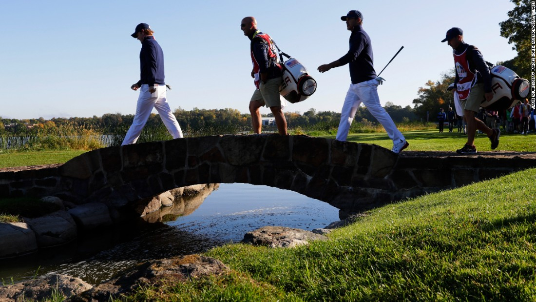 Brandt Snedeker and Brooks Koepka of the United States walk across the bridge on the seventh hole with their caddies.