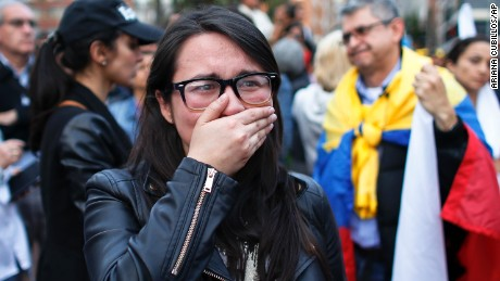 A supporter of the peace accord signed between the Colombian government and rebels of the Revolutionary Armed Forces of Colombia, FARC, cries as she follows on a giant screen the results of a referendum to decide whether or not to support the deal in Bogota, Colombia, Sunday, Oct. 2, 2016. Colombia's peace deal with leftist rebels was on the verge of collapsing in a national referendum Sunday, with those opposing the deal leading by a razor-thin margin with almost all votes counted.(AP Photo/Ariana Cubillos)