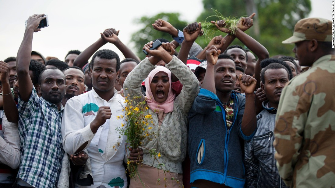 Security forces standby as Oromo people cross their wrists above their heads, a gesture that has become a symbol of Oromo anti-government protests.