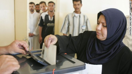 An Iraqi Sunni woman casts her vote at a polling station during a referendum on a new constitution of Iraq in the western town of Fallujah, 15 October 2005.