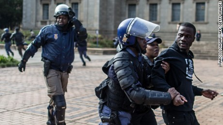 A student is detained by anti-riot police as they disperse a demonstration over fee increases at the Witwatersrand University in Johannesburg on October 4, 2016