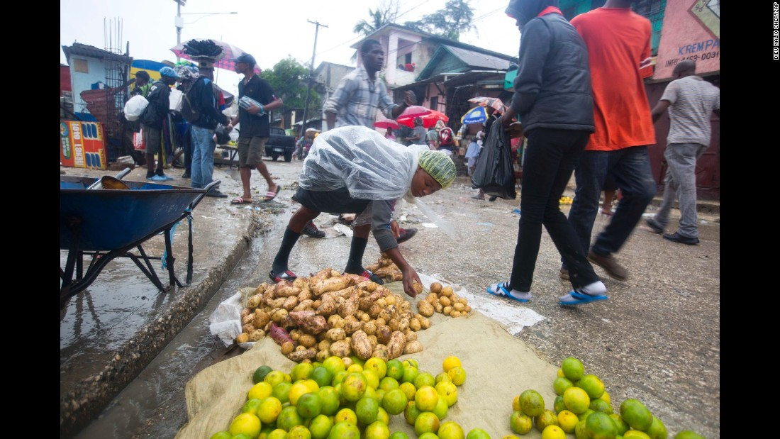A food vendor lays out goods for sale during a light rain in Port-au-Prince on October 4.