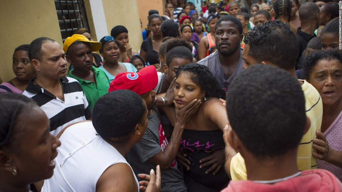 The mother of two girls who died in the storm is comforted near her home in Santo Domingo, Dominican Republic, on October 4. The girls were killed when a landslide caused by flooding breached the walls of their house.