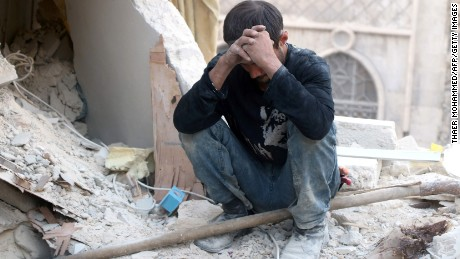 A Syrian man reacts as he sits on the rubble of destroyed buildings in Aleppo.