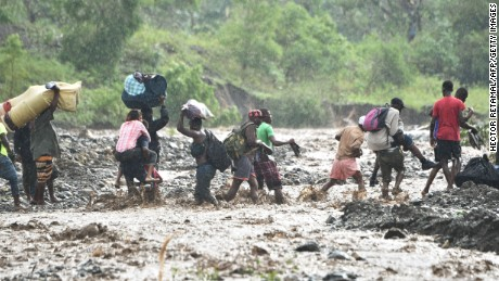 Haitian people cross the river La Digue in Petit Goave, southwest of Port-au-Prince, where a bridge collapsed during the rains of the Hurricane Matthew, October 5.