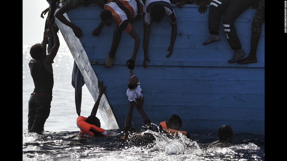 Migrants try to pull a child out of the water.