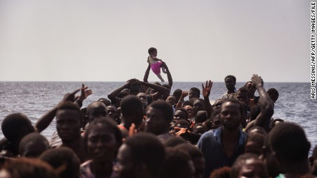 A child is lifted above a crowded boat as migrants wait to be rescued, October 4, 2016.