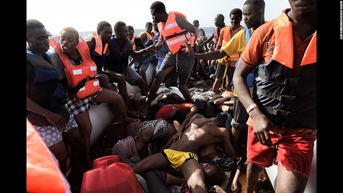"Migrants step over dead bodies <a href=""http://www.cnn.com/2016/10/06/europe/migrant-boats-libya-aris-messinis/index.html"" target=""_blank"">while being rescued</a> in the Mediterranean Sea north of Libya on Tuesday, October 4. Photographer Aris Messinis said the rescuers counted 29 dead bodies -- 10 men and 19 women, all between 20 and 30 years old. ""I've (seen) in my career a lot of death,"" he said. ""I cover war zones, conflict and everything. I see a lot of death and suffering, but this is something different. Completely different."""