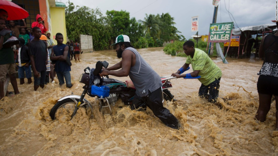 Men push a motorbike through a flooded street in Leogane on October 5. More than 300,000 people are in shelters across the country, the United Nations said.<br />