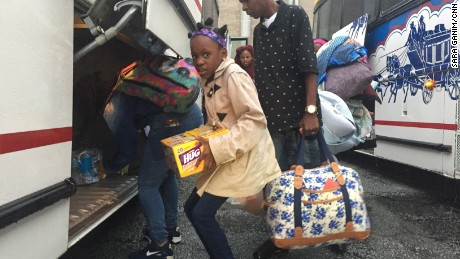 Families pack belongings onto a bus to evacuate.