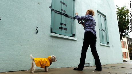Barbara Hearst tapes closed the storm shutters on the windows to her home with her dog, Bandit, nearby ahead of Hurricane Matthew on October 7 in Charleston, South Carolina.