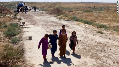 Amal (second from left) and her cousins approach the berm at the edge of Kurdish territory. In the background, others wait to be searched and called forward by Peshmerga.