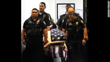 Palm Springs police officers carry the body of a fellow officer from a hospital to a hearse bound for the coroner's office Saturday in Indio, California.