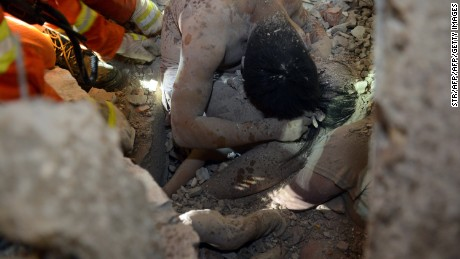 Rescuers try to save a young survivor who was protected by the body of her parents at an accident site after four buildings caved in during the early hours in Wenzhou in eastern China's Zhejiang province.