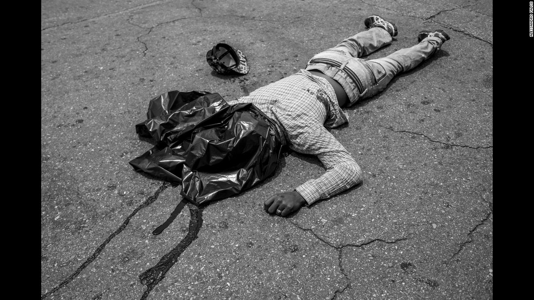 A young man lies dead in front of a supermarket where he allegedly just tried to rob a man, who reacted by shooting him in the stomach.