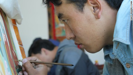 An art student paints a traditional thangka at an art school CNN was taken to on a government-approved tour.