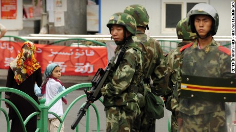 Chinese paramilitary policemen stand guard on a street in the Uyghur district of Urumqi city, Xinjiang, in July 2009.
